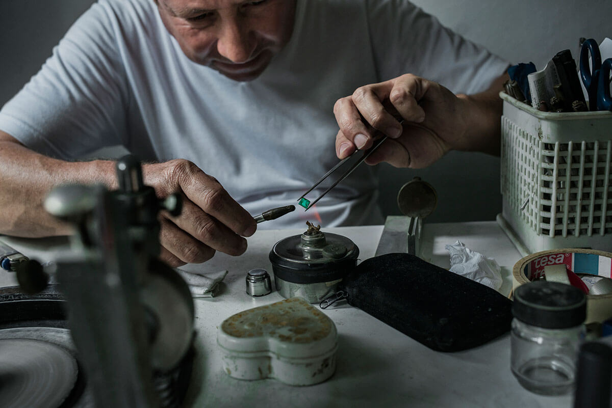 A carver in Muzo, Columbia, polishes an emerald in his workshop located in his house