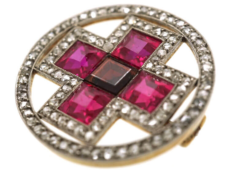 Synthetic rubies were used to decorate this Art Deco Circle Brooch With Cross Motif